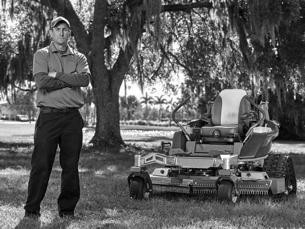Landscaper standing next to turf equipment powered by Vanguard